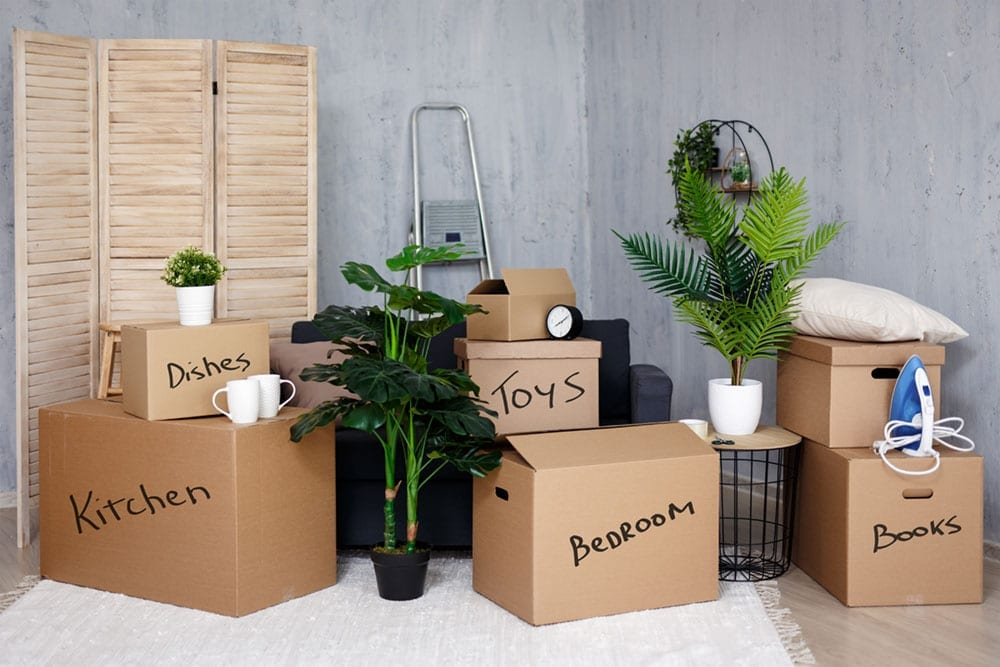 moving day and relocation concept - belongings packed in cardboard boxes in new house